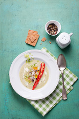 Zucchini cream soup with red pepper, cream, spices and balsamic cream on a wooden background, top view