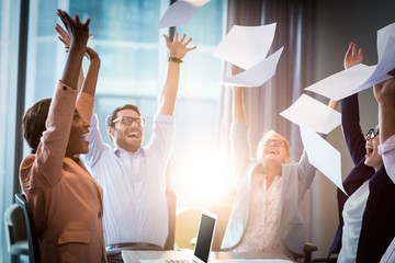 Business people throwing papers in the air