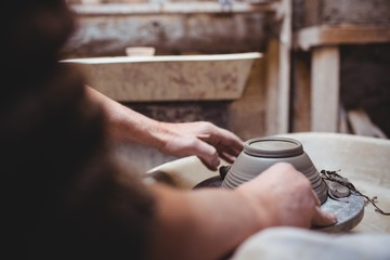 Cropped image of craftsperson making ceramic container