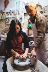 Female potter making ceramic container with colleague
