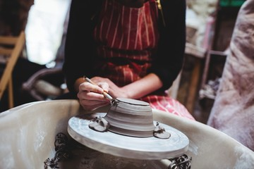 Midsection of potter preparing ceramic container