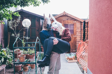 Couple of young beautiful redhead and blonde millennial woman and man wearing horse and rabbit mask, he is holding her outside thei home - married, couple concept