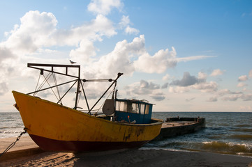 Yellow boat on the beach evening time