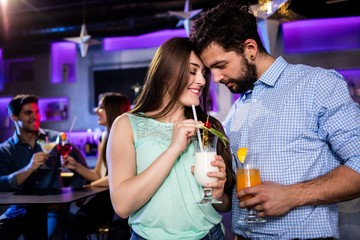 Couple embracing each other at bar counter while having cocktail
