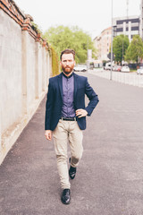 Young handsome caucasian bearded redhead millennial man walking outdoor in the city, looking in camera, serious - pensive, thoughtful, thinking future concept
