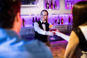 Barmaid serving drink to woman