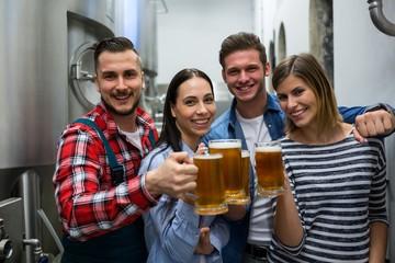 Brewers toasting beers at brewery