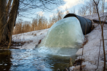 A culvert beneath a road has become mostly clogged with ice in northern Wisconsin
