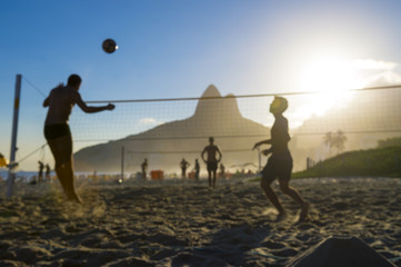 Silhouettes of Brazilians playing futevolei (footvolley) against a sunset backdrop of Dois Irmaos Two Brothers Mountain on Ipanema Beach, Rio de Janeiro Brazil