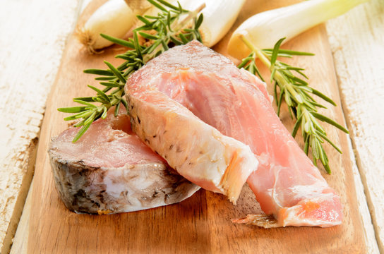 raw carp steak with rosemary and spring onions