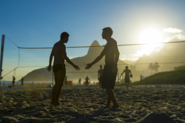 Defocus view of silhouettes of Brazilians shaking hands on a beach volleyball court in Rio de Janeiro, Brazil at sunset on Ipanema Beach