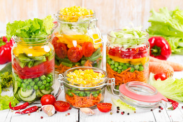 Prepared for canning colorful vegetables in glass jars on wooden