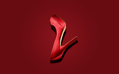 Red high heel shoe on red background