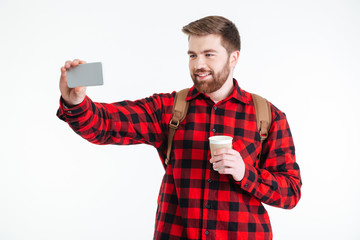 Man holding cup with coffee and making selfie photo