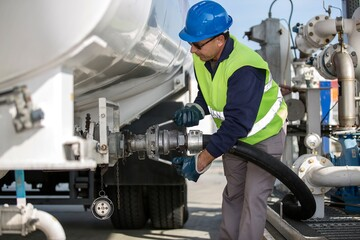 Male worker pumping fuel at fuel depot