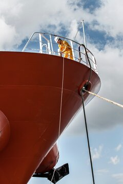 Worker fastening ropes on oil tanker deck