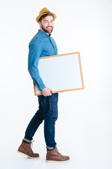 Smling young man holding blank board over white background