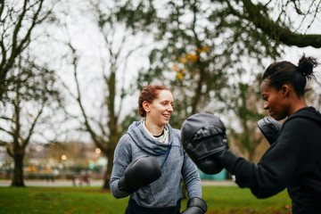 Young adult female boxers training in park