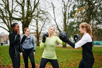 Female boxers punching each other in park