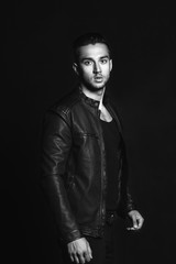 Fashion portrait of young man in black shirt poses over wall wit