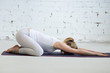 Pregnancy Yoga and Fitness. Portrait of young pregnant yoga model working out in loft with white walls. Pregnant fitness person practicing yoga at home. Prenatal Balasana, Child Pose