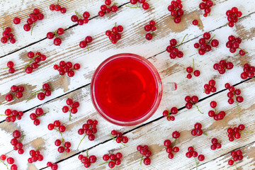 freshly squeezed red juice, and bunches of red currants on a white wooden table with old paint. closeup flat lay