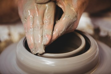 Cropped hands of craftsperson in pottery workshop