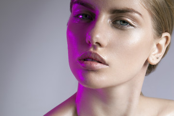beautiful girl with nudity make on the wet face up and pink backlight portrait