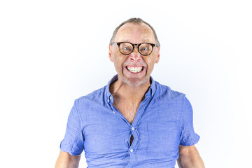 Portrait of angry and furious man with glasses in tight blue shirt.