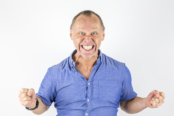 Portrait of angry and furious man in tight blue shirt.
