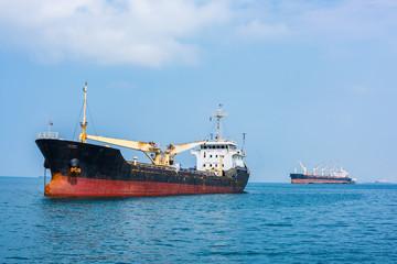 Cargo ships drop anchor at the harbor.