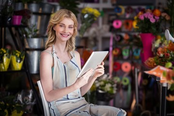 Smiling female florist using digital tablet in florist shop