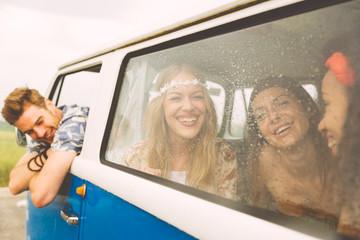 Hippie friends having fun into a vintage van, taking a break after long driving