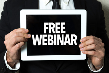 Business man holding tablet with the text: Free Webinar