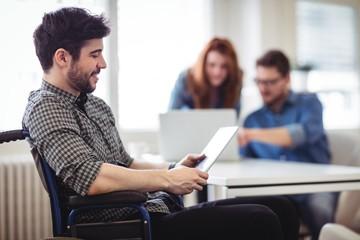 Businessman on wheelchair using digital tablet