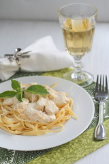 Fettuccine with chicken in a creamy sauce served with a glass of wine
