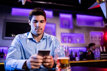 Man using mobile phone at bar counter