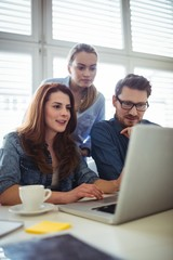 Businesswoman with coworkers looking at laptop
