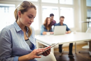 Businesswoman using digital tablet against coworkers