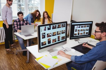 Photo editor working on computer against coworkers