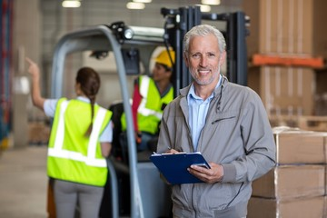 Portrait of worker holding a clipboard and looking the camera