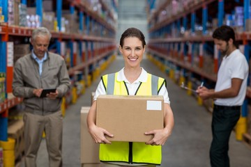 Focus on worker is holding cardboard box and smiling