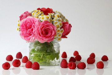 Summer cheerful bouquet of roses and daisies flowers and raspberries. Floral still life with bouquet of pink roses and white mini chrysanthemums in a vase and ripe raspberries. Flower home decoration.