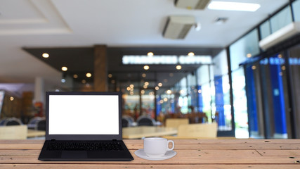 Laptop and coffee cup on wooden table with copy space and blurre