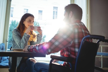 Happy woman looking at boyfriend at cafe