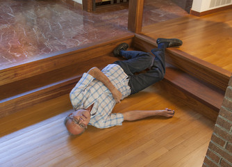 Senior man fell down the stairs onto a wood floor