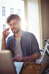 Portrait of happy man listening to cellphone at cafeteria