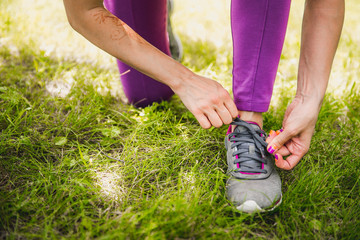 Running shoes being tied by women getting ready for jogging. focus on hands.