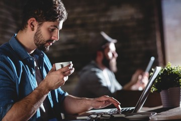 Side view of man drinking coffee while working on laptop