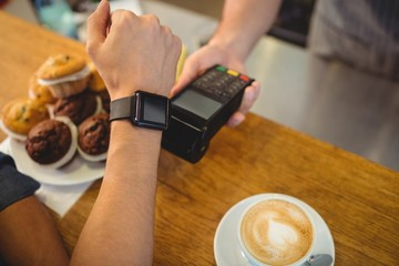 closeup of customer paying barista with smartwatch